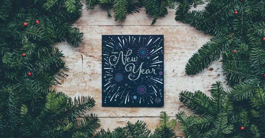 Beautifully written sign signaling the start of the New Year, surrounded by pine boughs.